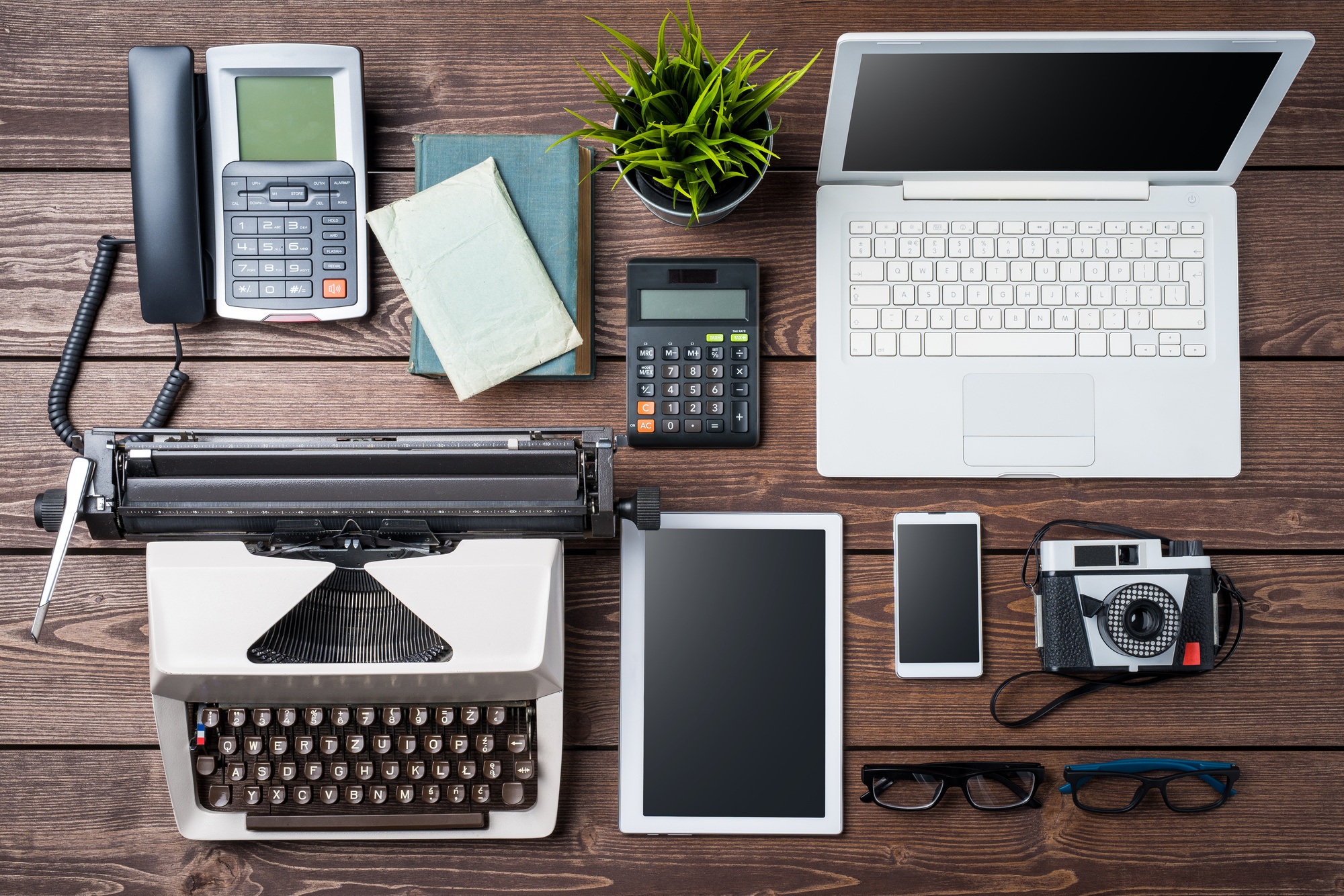 technology products laid out on a wooden table such as a typewriter, ipad, phone, camera, laptop, etc.